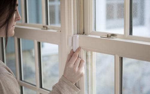 Woman Installing Window Sensor